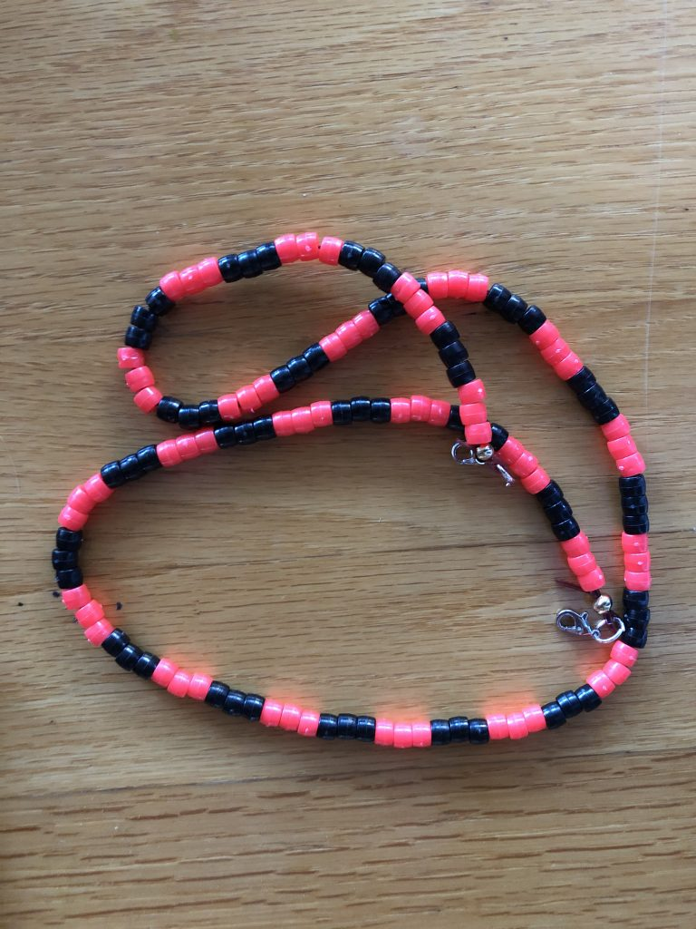 A completed mask holder in red and black beads.
