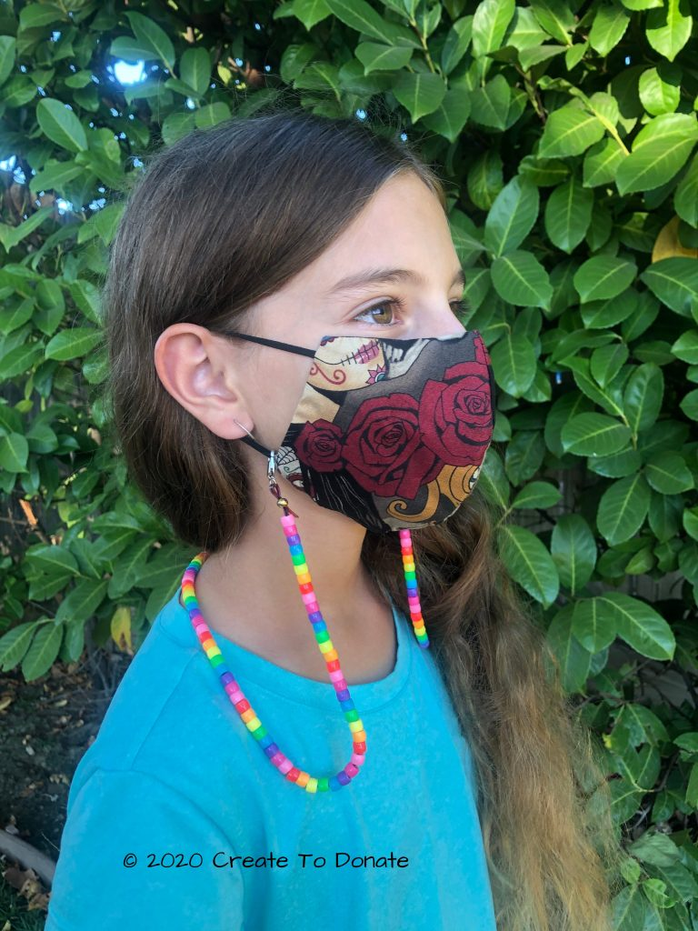Child wearing a mask holder attached to her mask.