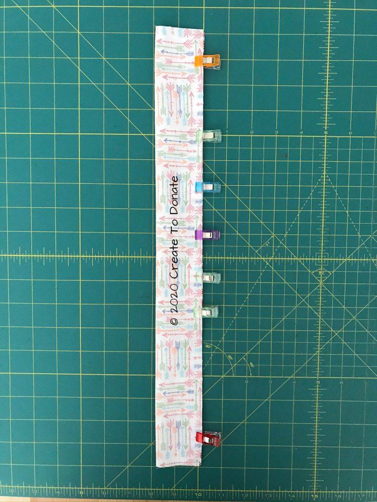 Fold fabric scrunchie scrap fabric in half and clip