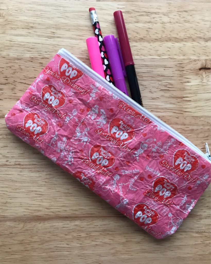 Zipper pouch made from candy wrappers with pencils peeking out.