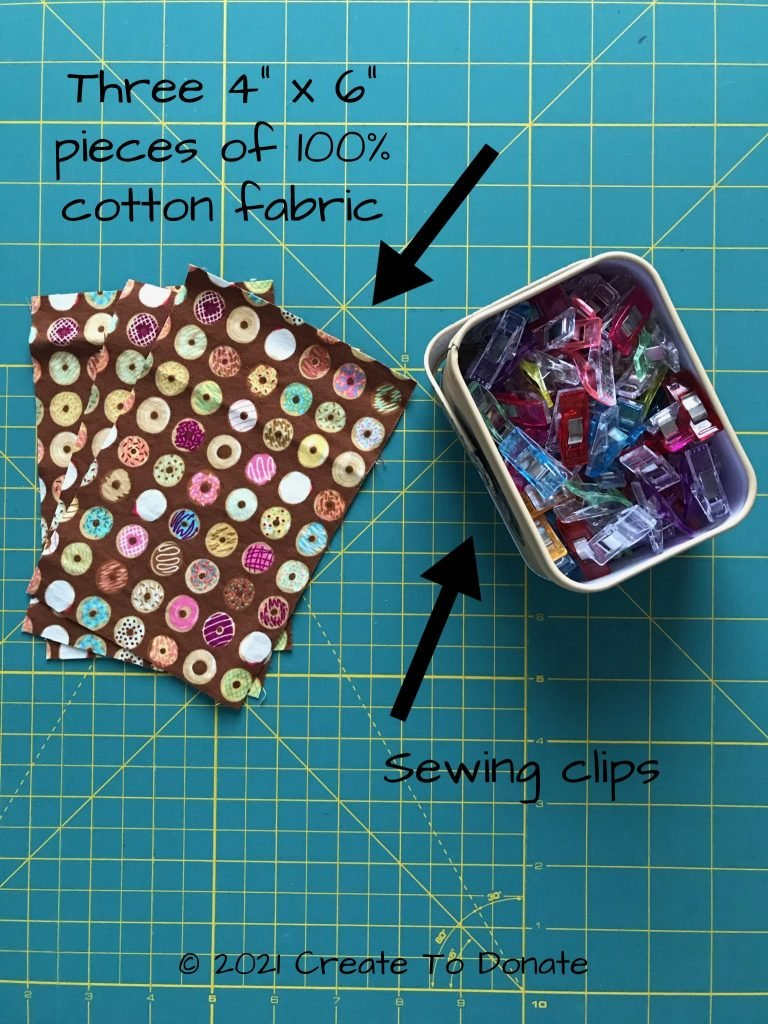 Materials for face mask pouch pattern displayed. Three pieces of fabric at 4 x 6 and sewing clips.