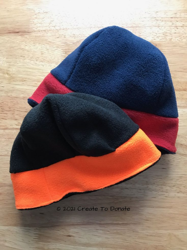 Examples of completed reversible fleece hat pattern in black and neon and red and blue.
