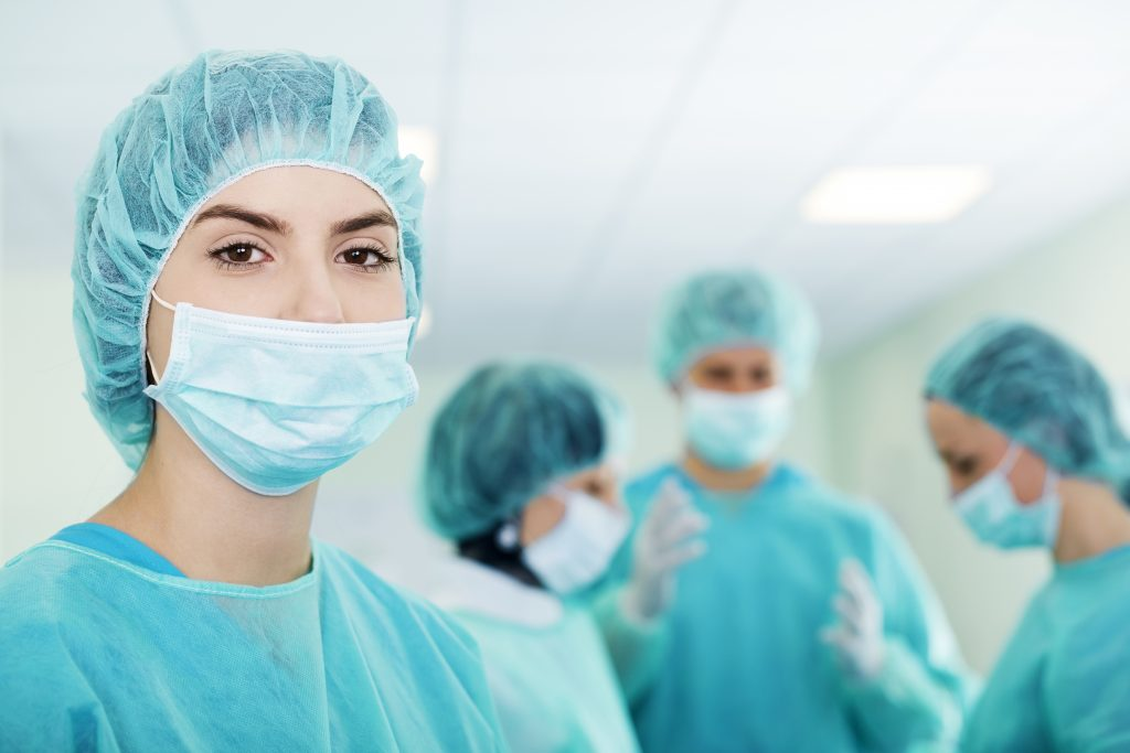Women in medical scrubs with a surgical cap and mask on in hospital setting.