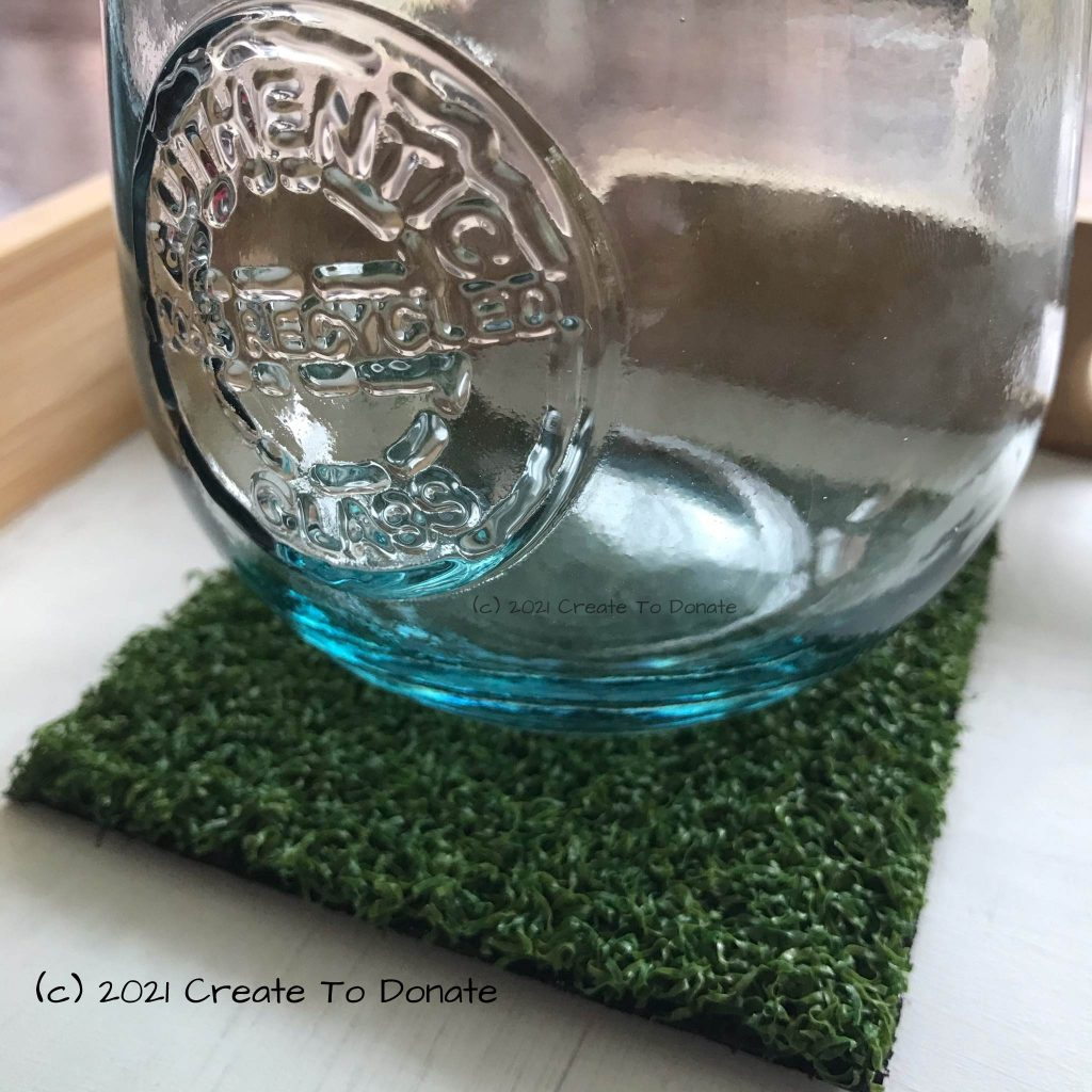Glass on a drink coaster made from turf.