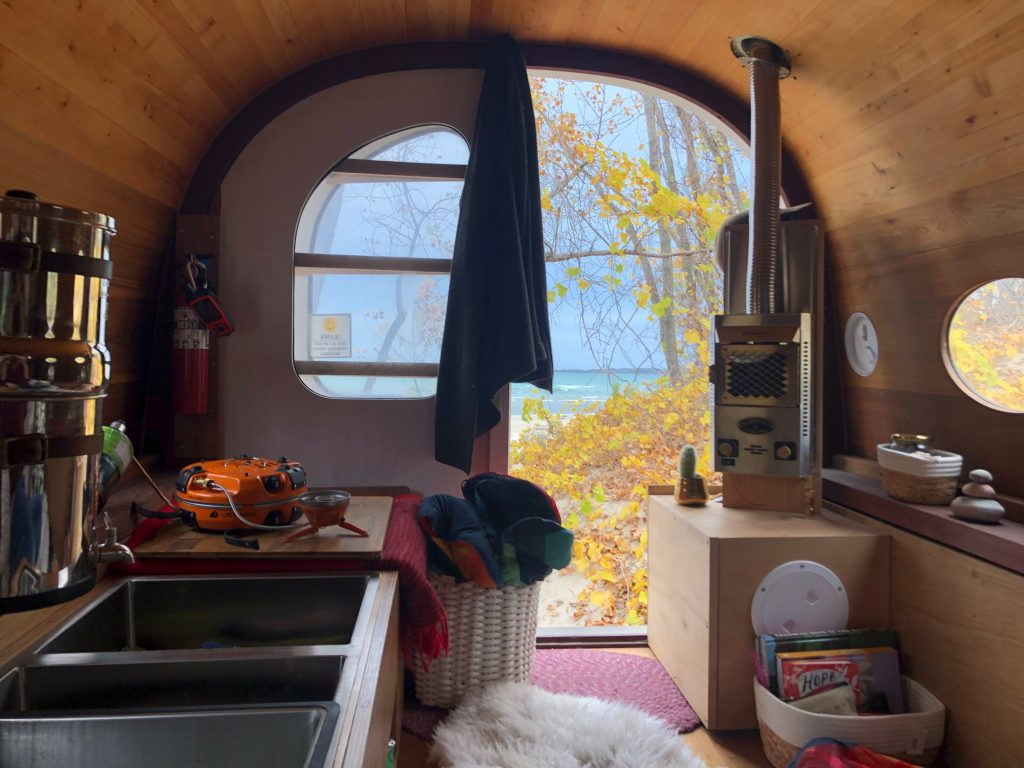 Tiny home kitchen with view of outside.