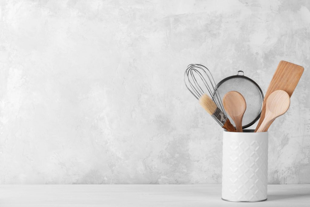 Baking tools in a white ceramic container.