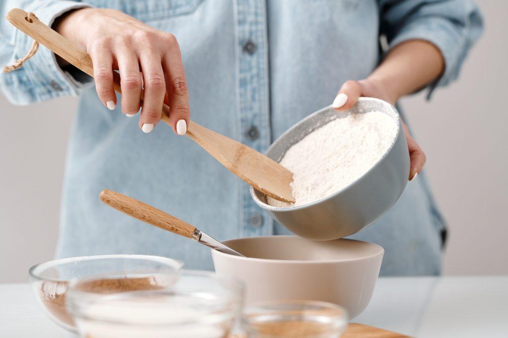 Hands adding flour to a bowl.