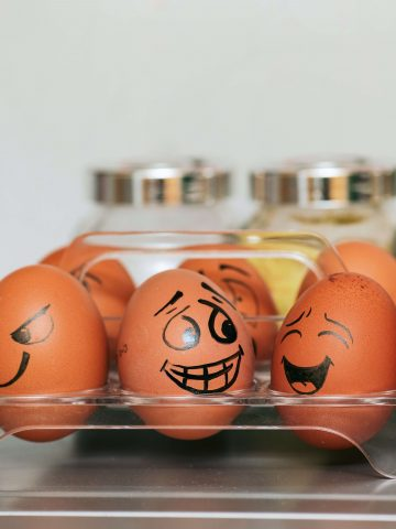 Eggs with silly faces drawn on them to showcase cookie recipes without eggs.