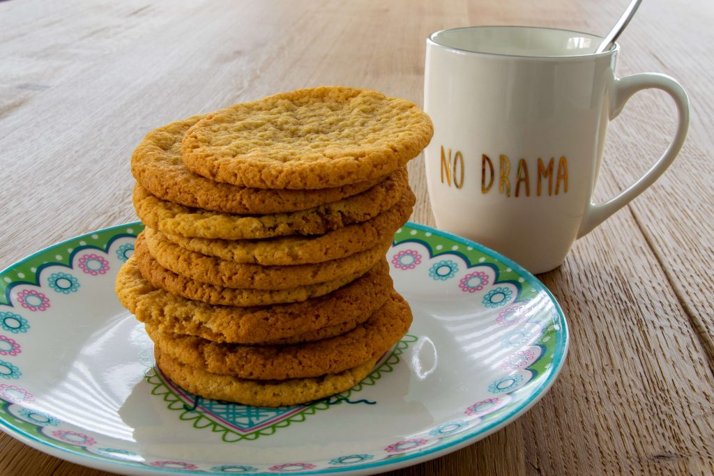 Cookies stacked on a plate and a cup of coffee in a mug that says no drama.