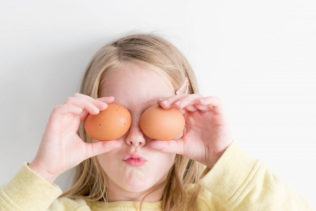 Young girl with two eggs in front of her eyes.